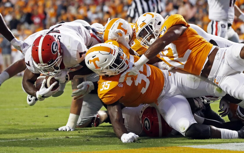 Georgia running back D'Andre Swift (7) dives across the goal line for a touchdown as he is defended by Tennessee linebacker Daniel Bituli (35) and defensive back Shawn Shamburger (12) in the first half of an NCAA college football game, Saturday, Oct. 5, 2019, in Knoxville, Tenn. (AP Photo/Wade Payne)