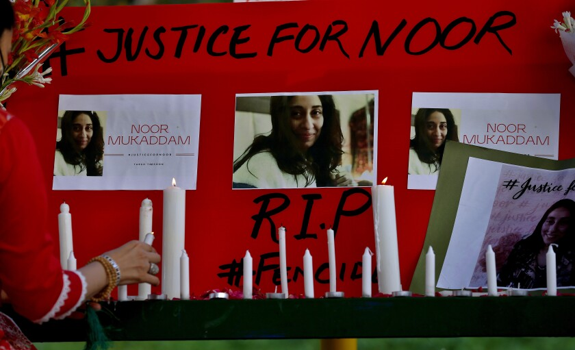 A women's rights activist places a candle beside a poster with pictures of slaying victim Noor Mukadam.