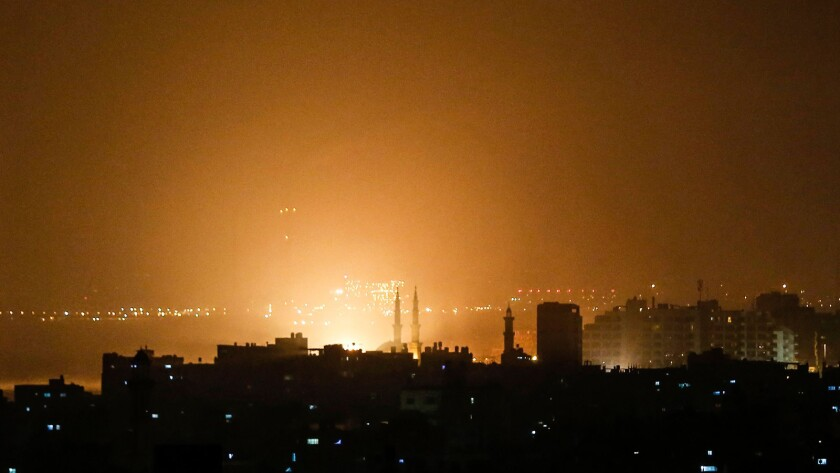 The sky above buildings on the Gaza Strip glows orange during an Israeli air strike late Thursday.