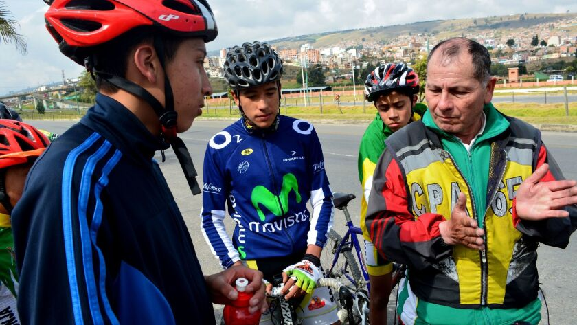 Fabio Casas, right, a trainer at the Santiago de Tunja cycling club, instructs Steven Motavita and other riders during an October practice in Boyaca, Colombia.