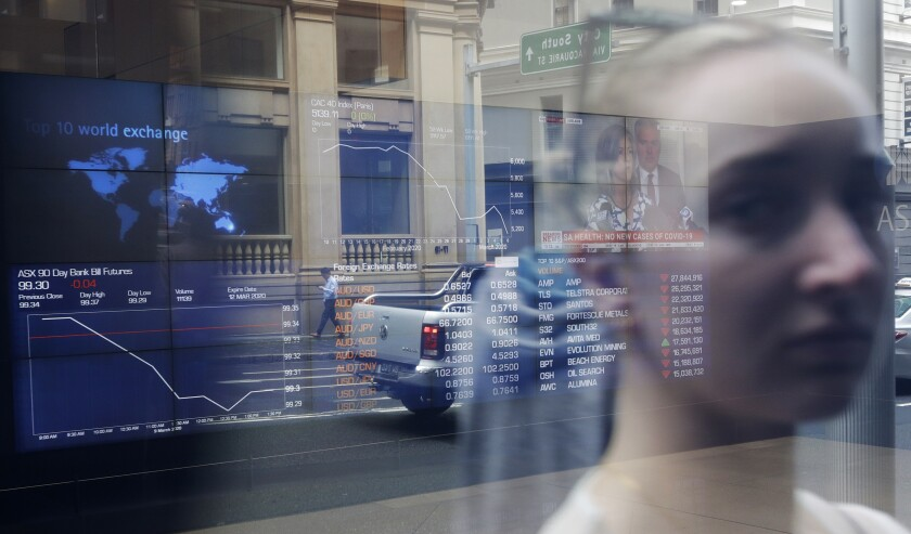 A woman's image is reflected in a window at the Australian Stock Exchange in Sydney on Monday.