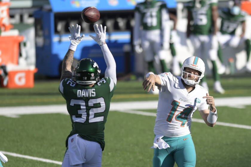 Ashtyn Davis (32), izquierda, de los Jets de Nueva York, trata de bloquear un pase del quarterback Ryan Fitzpatrick, de los Dolphins de Miami, en el duelo de NFL del domingo 29 de noviembre de 2020, en East Rutherford, Nueva Jersey. (AP Foto/Bill Kostroun)