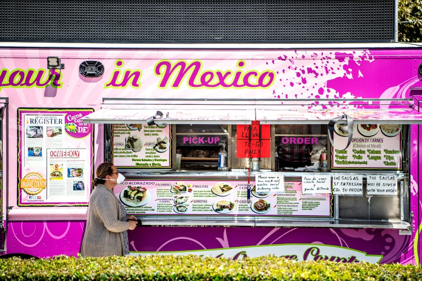 A customer wearing a mask places an order at Alebrijes taco truck on Wednesday, April 22, 2020 in Santa Ana.