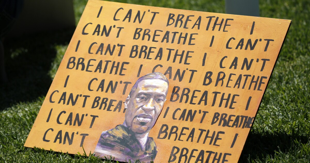 A sign at an Irvine protest showing the words 'I can't breath' and a portrait of George Floyd.