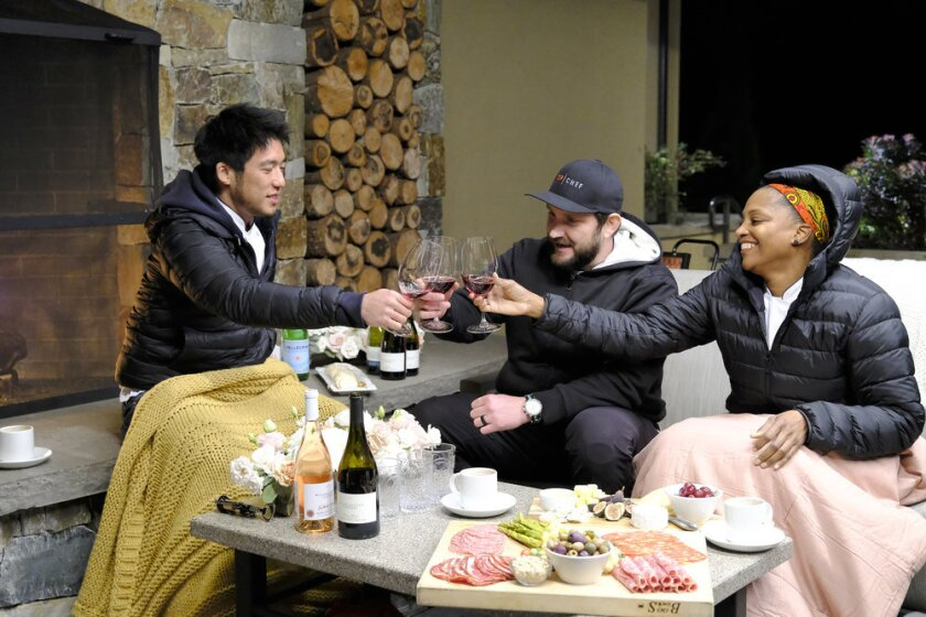 Three chefs toasting around a cheese and charcuterie board