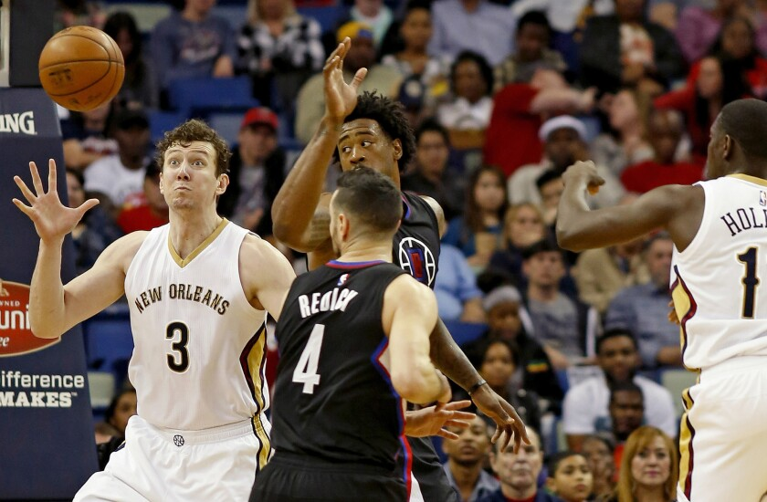 Pelicans center Omer Asik (3) receives a pass from guard Jrue Holiday past Clippers guard J.J. Redick (4) and center DeAndre Jordan in the first half.