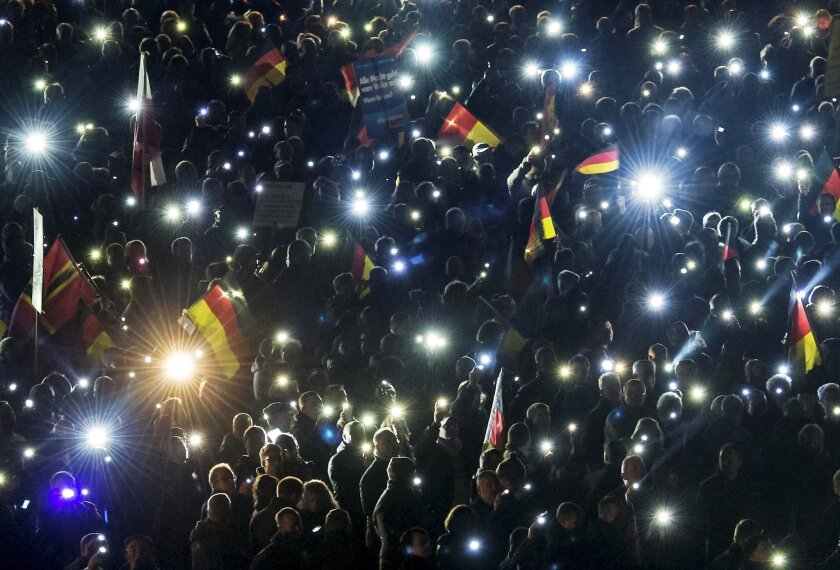 Thousands hold up the glowing displays of their mobile phones during a demonstration initiated by the Alternative for Germany (AfD) party against what they call the uncontrolled immigration and asylum abuse in Erfurt, central Germany, Wednesday, Nov. 4, 2015. (AP Photo/Jens Meyer)
