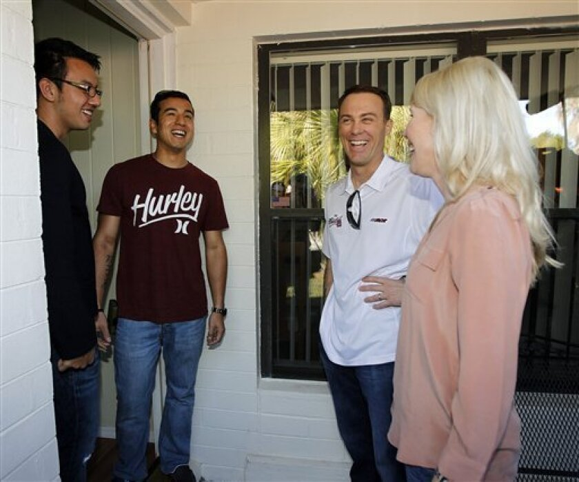 In this image provided by HHP Photo, NASCAR driver Kevin Harvick, second from right, and his wife DeLana, right, deliver Daytona 500 tickets to Justin Ryter and Jason Ryter, twin brothers who completed four years of active duty in the United States Marine Crops and recently returned home, Wednesday, Feb. 20, 2013, in Daytona Beach, Fla. (AP Photo/HHP Photo, Harold Hinson) MANDATORY CREDIT; NO SALES