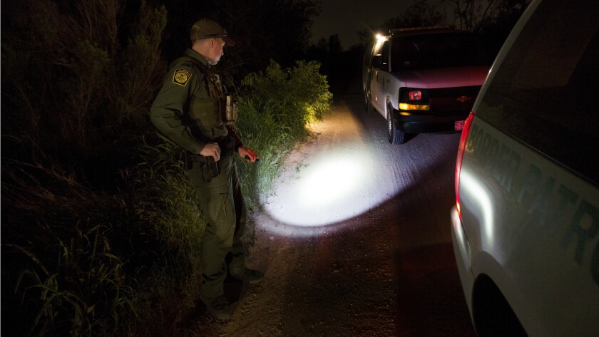 Border Patrol Agent Richard Schweitzer keeps an eye on migrants who had just illegally crossed the R