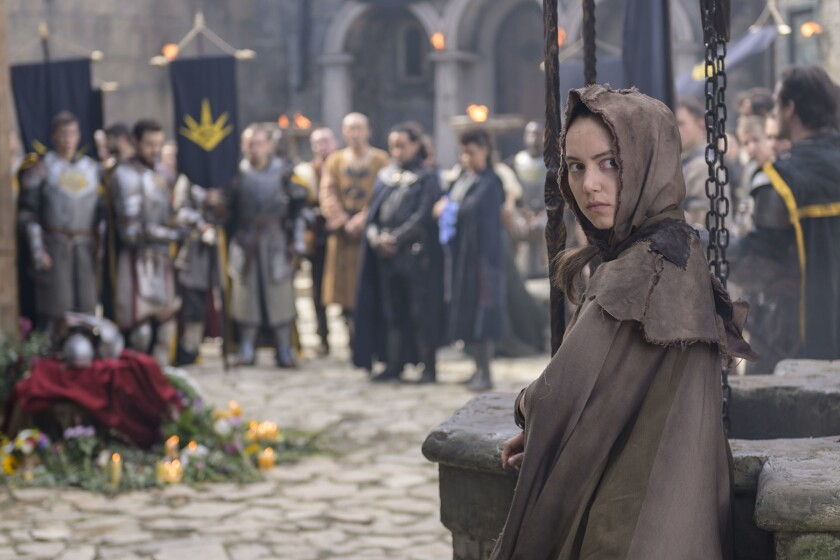 A woman in medieval garb stands in the foreground while villagers stand in the background