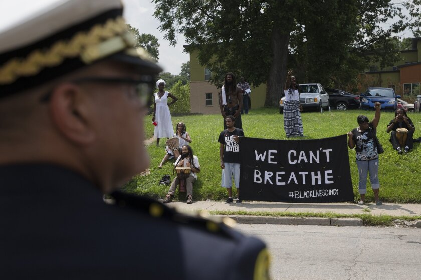 Cincinnati Police Chief Jeffrey Blackwell stands across the street from protesters outside the funeral service for Samuel DuBose this week. On Wednesday, a University of Cincinnati policeman was indicted on a murder charge in DuBose's death.