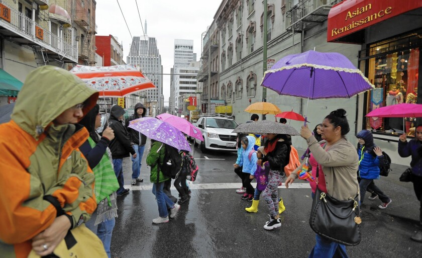 Pedestrians take cover in the Chinatown district of San Francisco as a powerful storm rolled into the Bay Area.