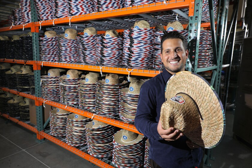 Anthony Lora, founder of the Hemlock Hat Co., at his company's Vista warehouse and headquarters with his hats with their characteristic colorful designs under the brims.