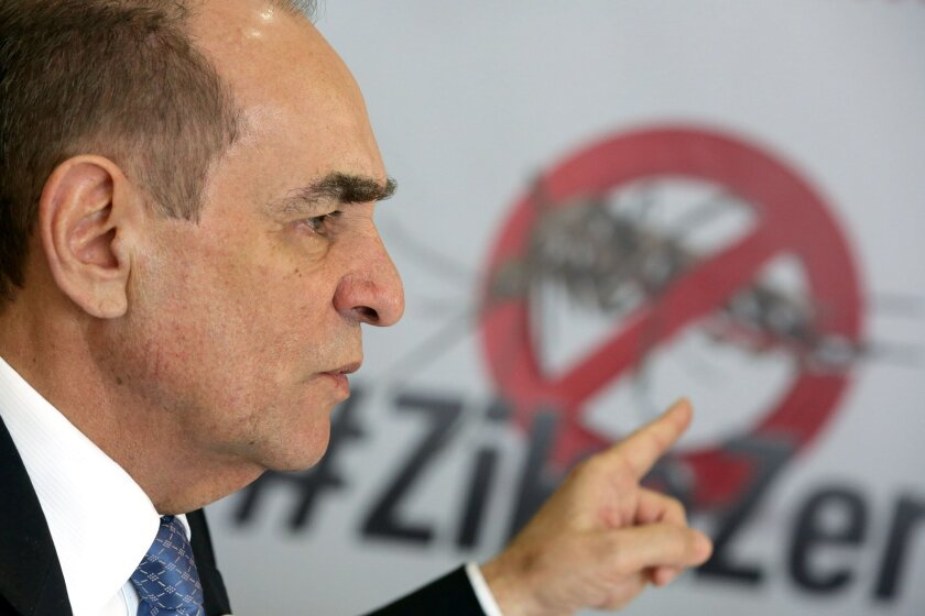 """Brazil's Health Minister Marcelo Castro speaks during an interview at the Health Ministry headquarters, in Brasilia, Brazil, Friday, Feb. 12, 2016. Castro made his remarks with a poster with an image of an Aedes aegypti mosquito and a text in Portuguese that reads """"One Mosquito is not stronger that"""