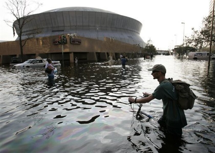 FILE - In this Aug, 31, 2005 file photo, a man pushes his bicycle through flood waters near the Superdome in New Orleans after Hurricane Katrina left much of the city under water. (AP Photo/Eric Gay, File)