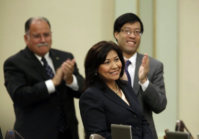FILE -- In this May 16, 2013 file photo,  Assemblywoman Norma Torres, D-Pomona, receives applause from members of the Assembly,  including Assemblymen Jose Medina, D-Riverside, left, and Richard Pan, D-Sacramento, after winning the 32nd District Senate seat in a special election.  Torres was 5 when