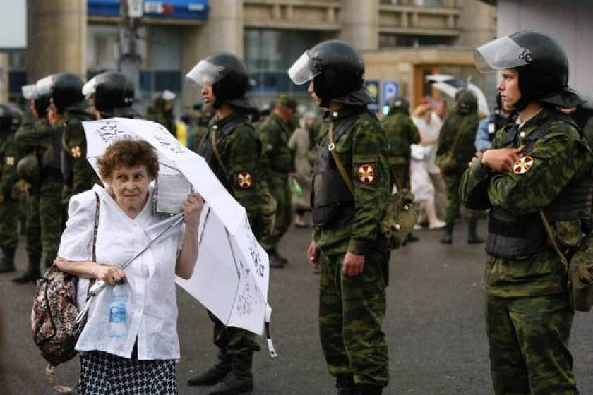A woman wearing white to symbolize the Russian opposition movement passes a line of police officers after a massive demonstration in central Moscow.
