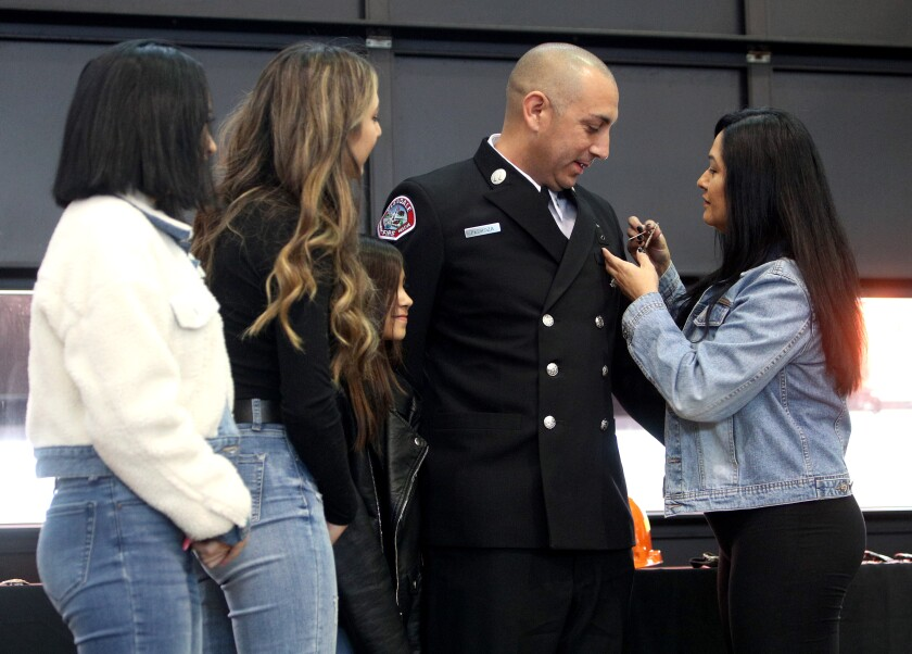 Glendale Fire Department Capt. Gil Pedroza is pinned with his new badge by his wife, Veronica Pedroza, along with their children, Sam, Alex and Charly, looking on at left, during the agency's badge-pinning and promotion ceremony at Fire Station 21 in on Thursday, Jan. 16, 2020.