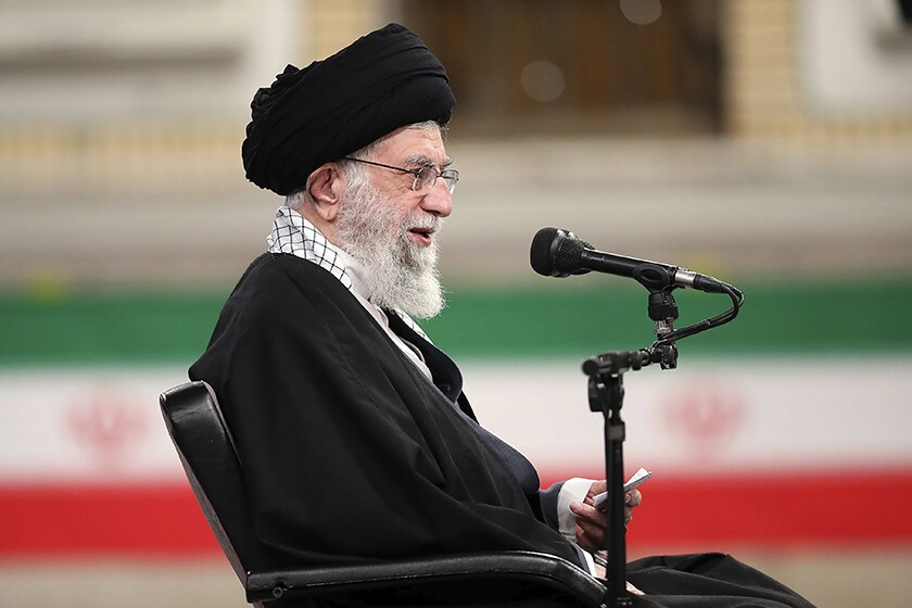 Supreme Leader Ayatollah Ali Khamenei sits in a chair next to a microphone