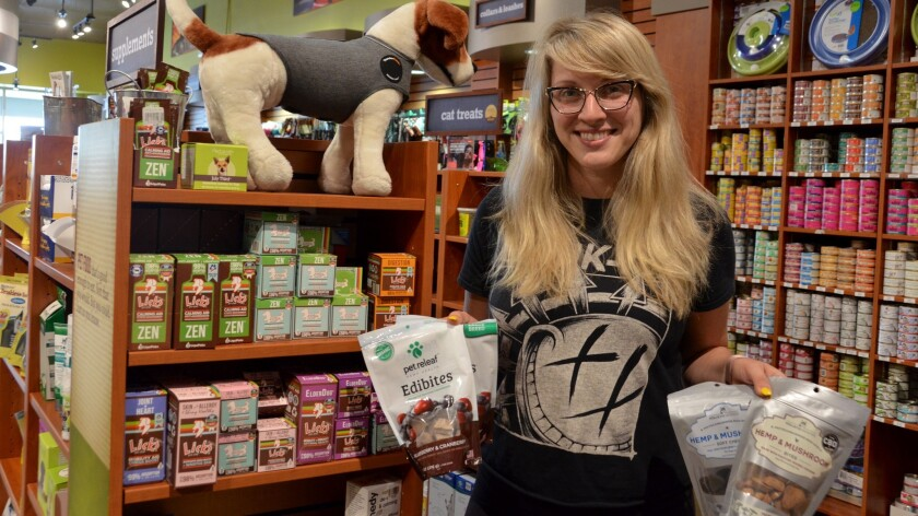 Chelsie Turner, an employee of Kriser's Natural Pet in Newport Beach, holds pet calming products, including CBD, or cannabidiol, items.