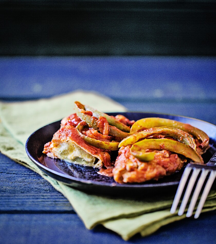 Chiles rellenos, Mexican cheese-stuffed peppers, covered in a tomato-based sauce with onions and bell peppers.