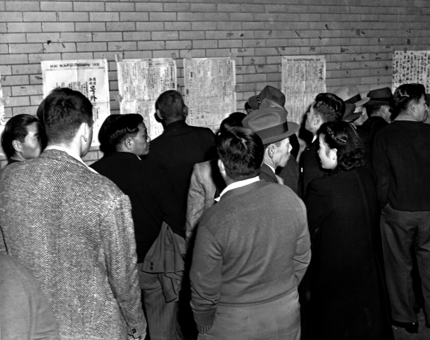 Japanese and Japanese American residents in Los Angeles scan the Rafu Shimpo as they learn news of the Pearl Harbor attack.