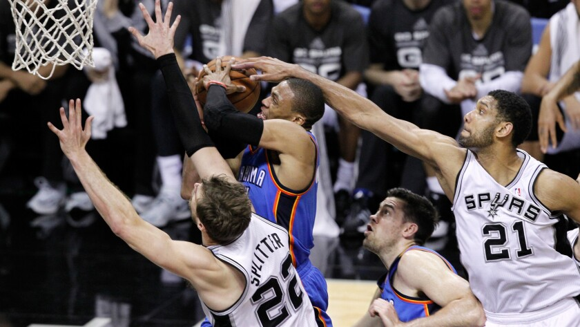 Oklahoma City's Russell Westbrook, center, goes up for a shot between San Antonio Spurs teammates Tiago Splitter, left, and Tim Duncan, right, during the Spurs' 122-105 win in Game 1 of the Western Conference finals Monday.