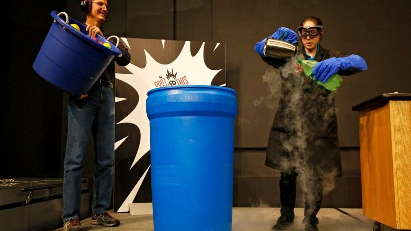 """Fleet Science Center demonstrator Ariana Walker hosted the """"Don't Try This at Home!"""" live science show on Sunday morning. Walker demonstrated several experiments with nitrogen, here, blowing on the liquid to create a gas cloud."""