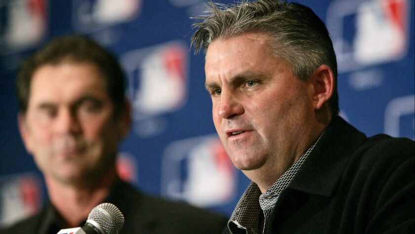 FILE - In this Dec. 7, 2005, file photo, San Diego Padres general manager Kevin Towers, right, peaks