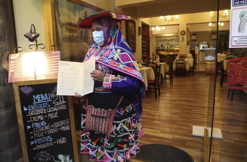 Una camarera vestida con ropa tradicional muestra el menú de un restaurante vacío en medio de la pandemia de COVID-19 en Cusco, Perú, el viernes 30 de octubre de 2020. La pandemia ha provocado que Cusco, la capital de los Incas y que vive casi por completo del turismo internacional, se encuentre sumida en la peor crisis de su historia reciente. (Foto AP/Martín Mejía)