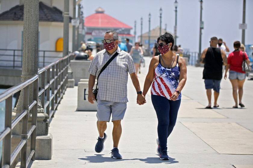 Danny Lopez of Chino Hills and his date Frances Pluma of Norwalk stroll on in Huntington Beach