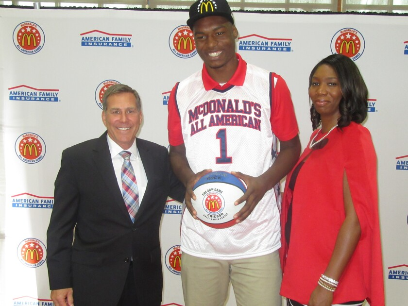 (Left) Brooks Hoven, a San Diego County McDonald's representative, presented Brandon McCoy (center) with a jersey and hat at the Feb. 3 event. (Right) Brandon's mom, Mildred Davis