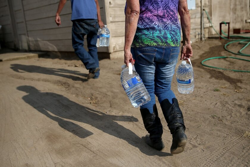 Drinking water is delivered in April to a resident in Porterville, Calif., which has no running water.