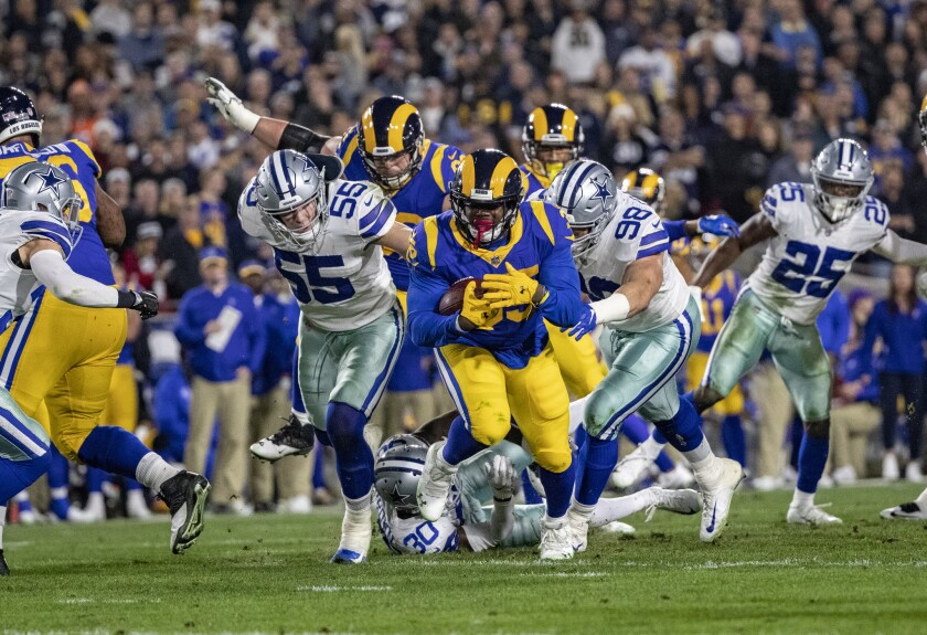 Rams running back C.J. Anderson (35) breaks through a big hole for a gain against the Cowboys during the first half Saturday