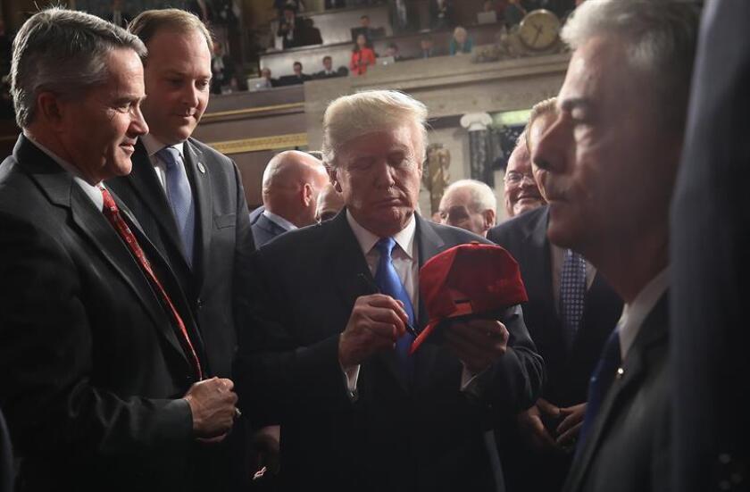 El presidente estadounidense Donald Trump (c) firma una gorra después de pronunciar su discurso sobre el Estado de la Unión ante el Congreso, en Washington (Estados Unidos). EFE/POOL