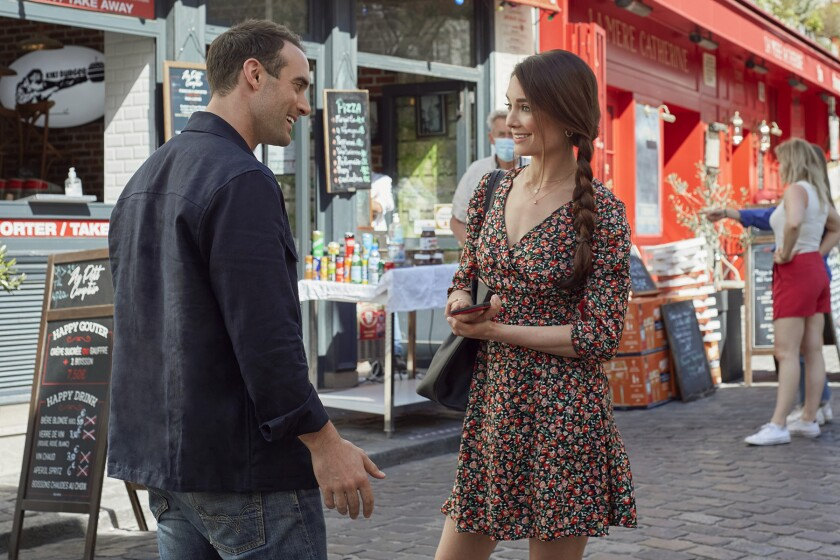 A man and a woman talk on a Paris street.