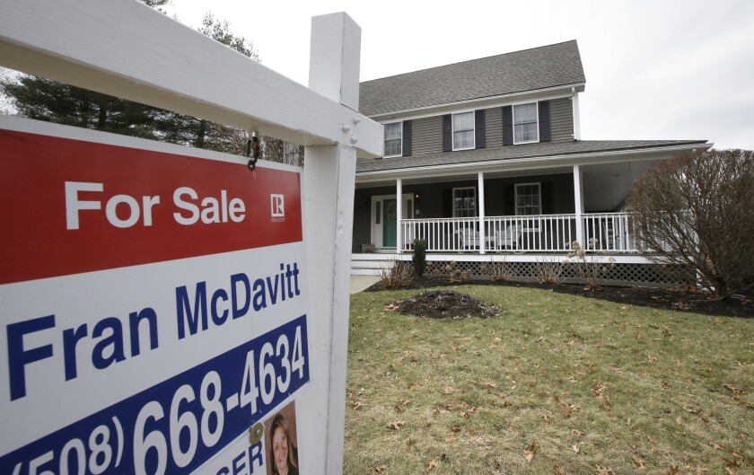 In this Friday, Feb. 23, 2018, photo a for sale sign stands in front of a house, in Walpole, Mass.