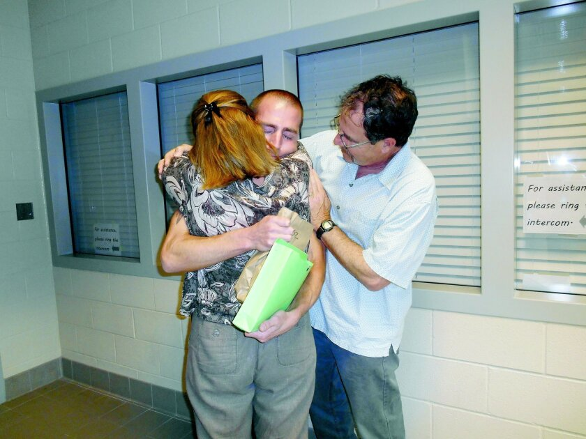 Uriah Courtney is embraced by his mother and stepfather upon his release from prison on May 6, 2013. Courtesy photo
