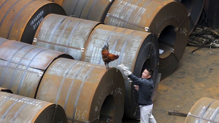 In this May 19, 2018, photo, a worker gestures to a rooster onboard a ship carrying rolls of steel p