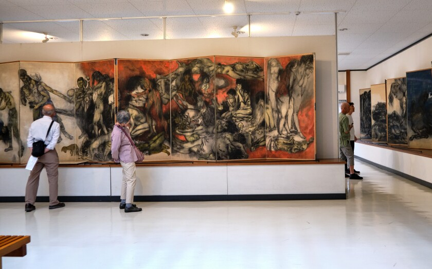 Visitors gaze at large-scale rice paper paintings that show bodies surrounded by flame