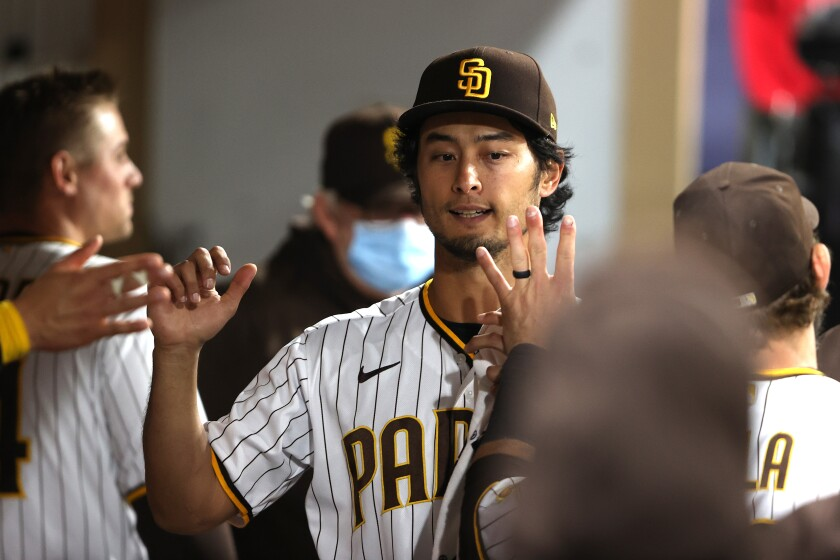 Yu Darvish is greeted in the dugout after scoring a run