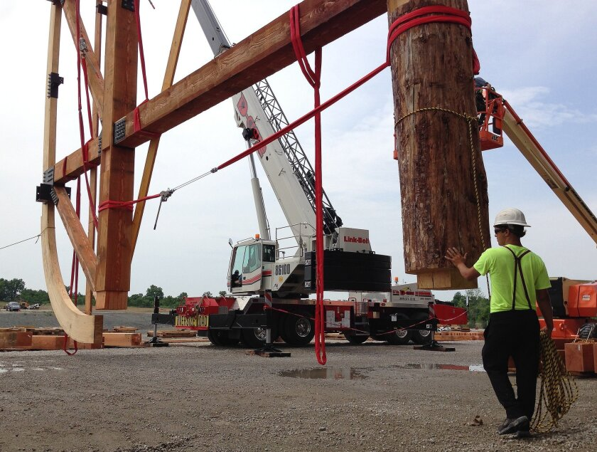 A wooden rib that is part of a ship based on the story of Noah's ark is raised into place in Williamstown, Ky., on Thursday, June 25, 2015. The Ark Encounter will be a religious tourist attraction when it opens next year. (AP Photo/Dylan Lovan)