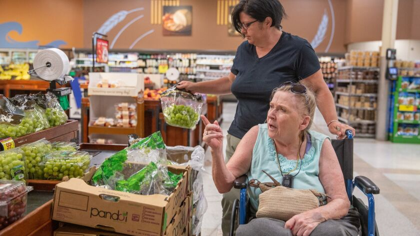 Wendy Matney, back, helps mother-in-law Glenna Smith shop for groceries at Kroger in Bristol, Va.,