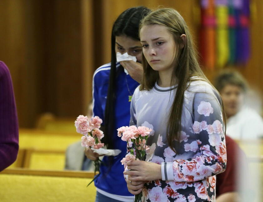 Rachel Marsh, right, and Selena Orozco, both 15, attend a prayer service after the mass shooting that left five dead at a mall in Burlington, Wash.