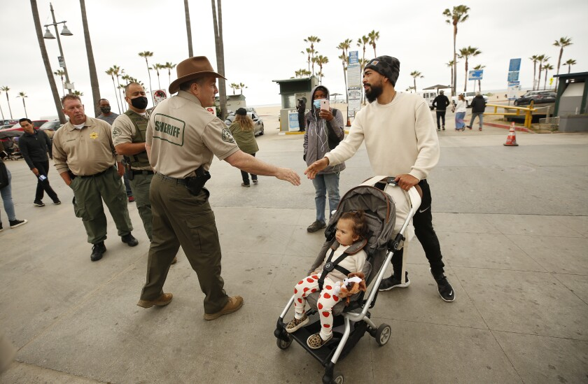 Sheriff Alex Villanueva shakes the hand of a man walking his baby in a stroller.