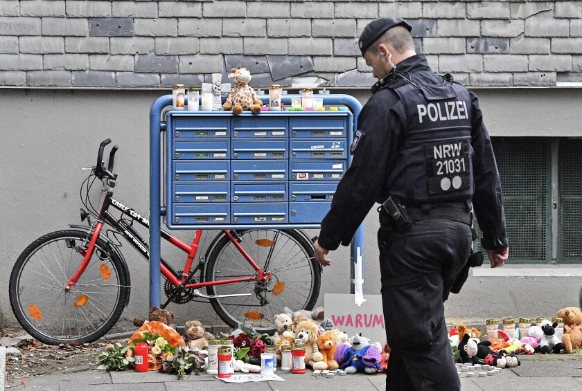 Police passes candles and teddy bears at the entrance of a house where five dead children were found in Solingen, Germany, Friday, Sept. 4, 2020. Police say five young children have been found dead on Thursday at the apartment in Solingen, their mother is suspected of killing them. Police said the children's 27-year-old mother later jumped in front of a train in Duesseldorf and was taken to a hospital with injuries. Only one child of the mother survived, who was send to his grandmother before. (AP Photo/Martin Meissner)