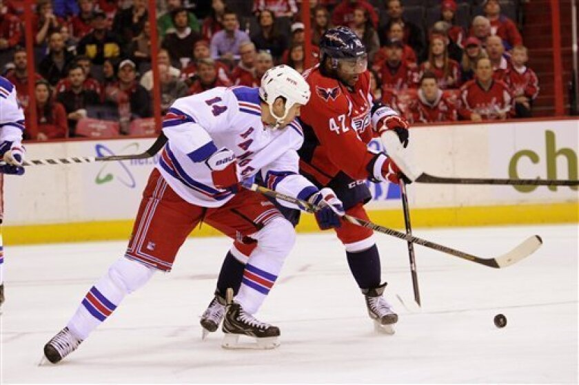 Washington Capitals right wing Joel Ward (42) battles for the puck against New York Rangers left wing Taylor Pyatt (14) during the first period of an NHL hockey game, Sunday, March 10, 2013, in Washington. (AP Photo/Nick Wass)