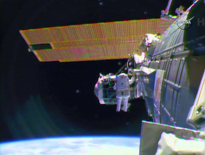 """In this image from television astronaut Barry """"Butch"""" Wilmore begins the spacewalk Saturday morning Feb. 21, 2015 to wire the International Space Station in preparation for the arrival in July of the international docking port for the Boeing and Space-X commercial crew vehicles. (AP Photo/NASA-TV)"""