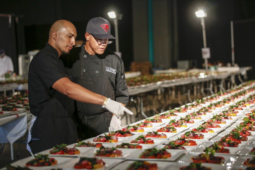Edgar Ulisses Flores, left, and James Rich -- trained by L.A. Kitchen -- prep salad dishes in the ki