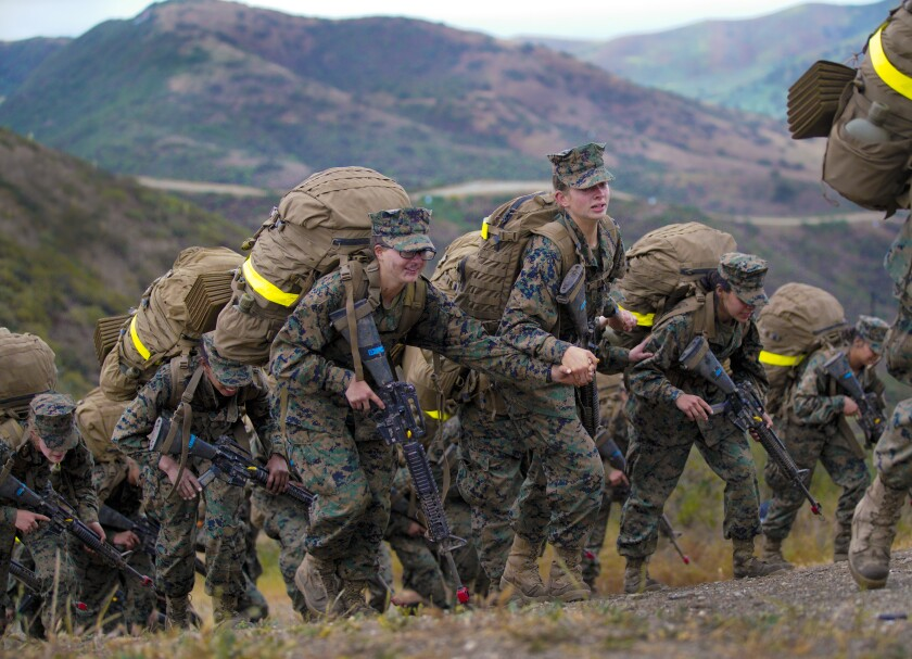 At Camp Pendleton, three women hold hands as they crest over the final ridge of the reaper during Marine boot camp